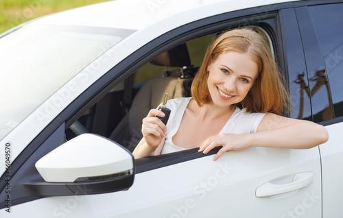 Leinwanddruck Bild woman driver with keys driving a new car