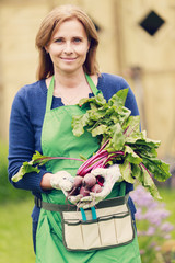 Woman with organic beets in a vegetable garden