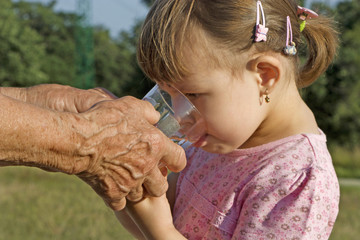 hands of the grandmother and water for the grandaughter