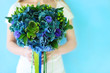 A wedding bouquet with hydrangea in blue and green colors outdoo