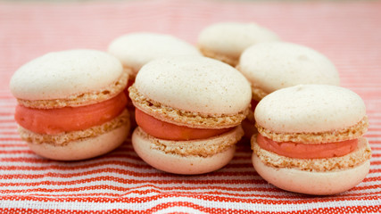 macaroons close up with orange cream and pink background