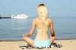 Quadro Woman meditating at beach