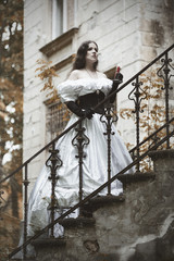 Mysterious woman in  Victorian dress. Stylized photo at old