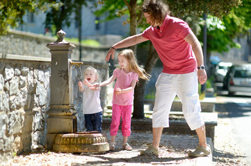 Two girls having fun with drinking water fountain