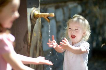 Two girls having fun with drinking water fountain
