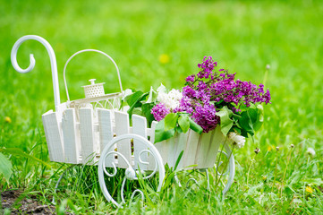 Decorative white cart with beautiful lilac flowers