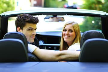 junges Paar sitzt im Cabrio