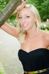 Portrait einer blonden Frau am Baum