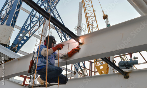 welder with protective mask welding metal and sparks - 66055915