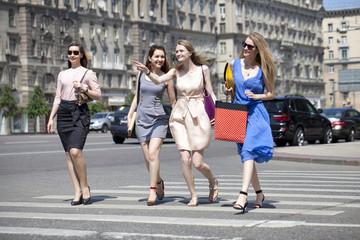 Four beautiful fashion girls walking on the street