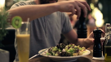 Man spicing up salad with salt and pepper in restaurant