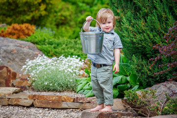 Happy kid holding up a bucket in the garden
