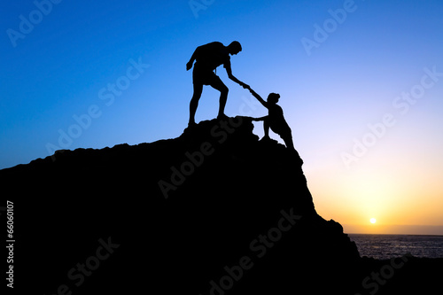 Leinwanddruck Bild Man and woman couple help silhouette in mountains