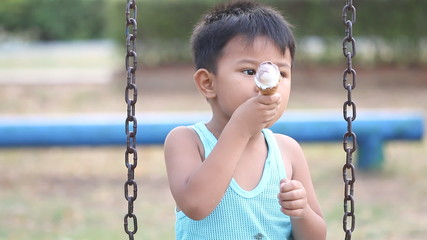 Little boy enjoys ice cream cone in playground.