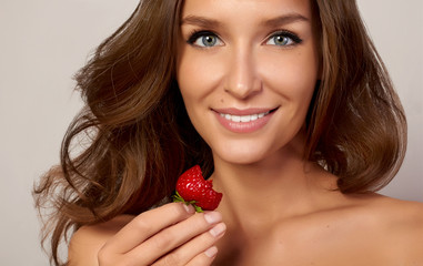 Beautiful young girl with white teeth eating strawberries