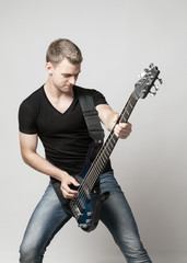 young male musician playing a six-string bass guitar isolated on