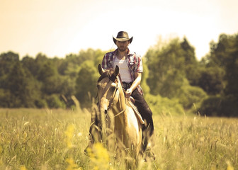 young cowboy man riding with horse