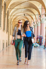 two girls walking in european city