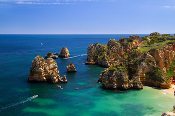 Blue water, boats, cliffs and beach in Portugal