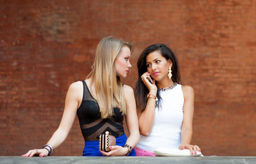 two girls standing one talking at phone