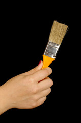 Woman hand holding paintbrush isolated on the black background
