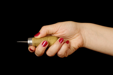 Woman hand holding awl isolated on the black