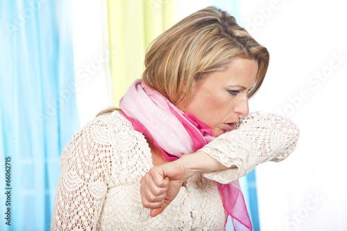 Frau hustet in ihren Ärmel - 66062715