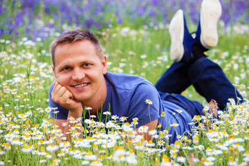 Portrait of a man in a flowery meadow.