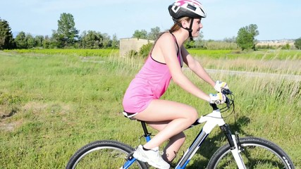 cheerful and healthy young woman riding mountain bike oudoor