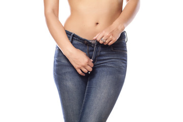 woman buttoning her jeans on white background