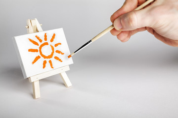 painter painting a sun on a small array