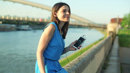 Woman listening music on smartphone by the river in the city