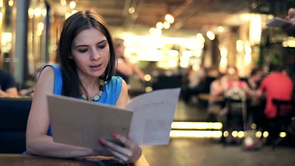 Young woman placing order to waiter in restaurant