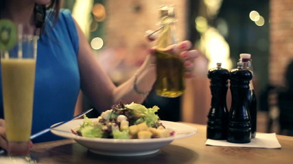 Woman pouring olive oil on tasty fresh salad in restaurant
