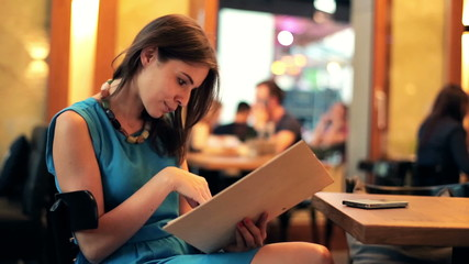 Young woman reading menu in restaurant