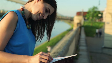 Young woman reading book by the river in the city