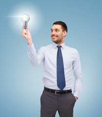 handsome businessman holding light bulb
