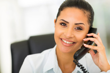 young businesswoman using landline phone