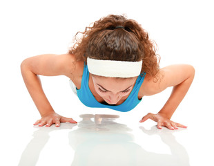 Young brunette woman doing push ups, isolated on white