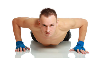 Young fitness man doing push ups on floor, studio shot isolated