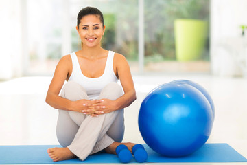 woman sitting on mat with exercise ball