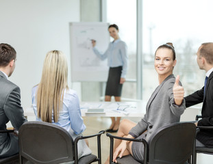 businesswoman with team showing thumbs up