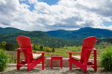 Two empty red chairs overlooking vineyards