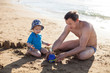 Father and son playing with sand at the beach