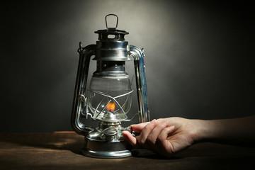 Hand lights a kerosene lamp on dark grey background