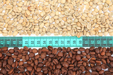 Raw green and roasted coffee beans and measuring tape close-up.