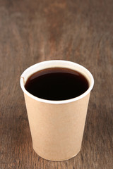 Paper cup of coffee on wooden table
