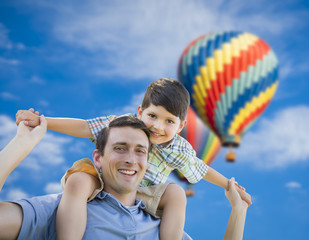 Father and Son Playing Piggyback with Hot Air Balloons Behind