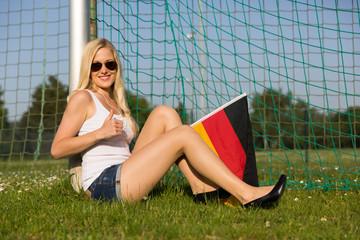 Attraktive Frau mit Deutschlandfahne zeigt Daumen hoch