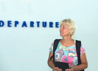 woman with a backpack and electronic device in airport departure